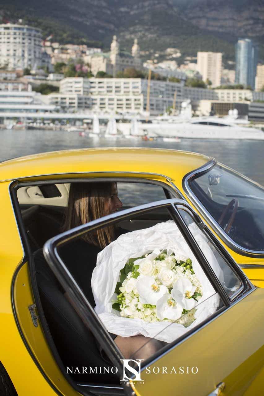 Une jolie jeune femme dans une voiture de prestige tenant un bouquet somptueux
